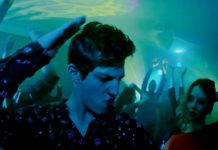 Ciemnowłosy chłopak bawiący się na imprezie