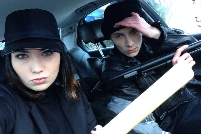 Chłopak i dziewczyna, oboje ubrani na czarno, dziewczyna na czarną czapkę z daszkiem, oboje siedzą w samochodzie