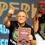 Mężczyzna w żółtych okularach i w czarnej koszulce, jedną ręką pokazuje znak zwycięstwa, drugą trzyma zdobytą nagrodę, w tle kobieta z mikrofonem