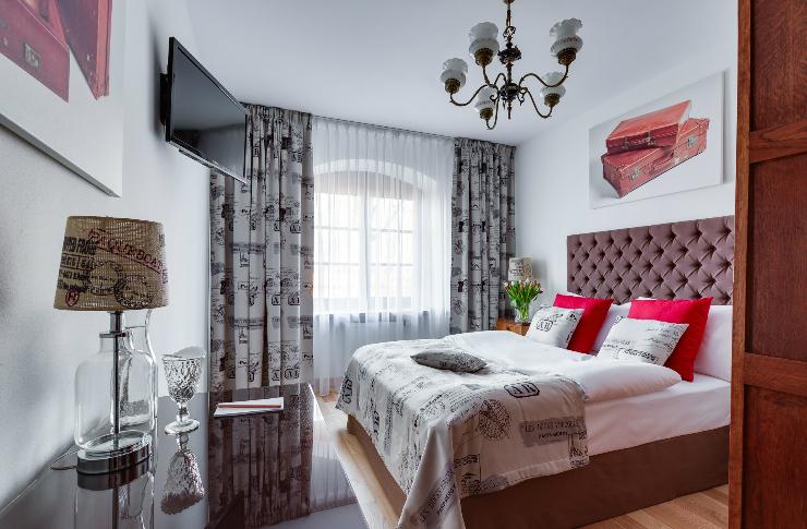 Pokój z dużym podwójnym łóżkiem, utrzymany w kolorystyce czerwono-szarej, duże okno, stolik z lampką