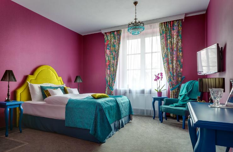 Wnętrze pokoju z ciemno-różowymi ścianami, kolorowym łóżkiem z żółtym oparciem i turkosową narzutą, stolik, telewizor