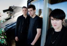 Dwóch chłopaków i dziewczyna, ubrani na czarno, stojący na balkonie