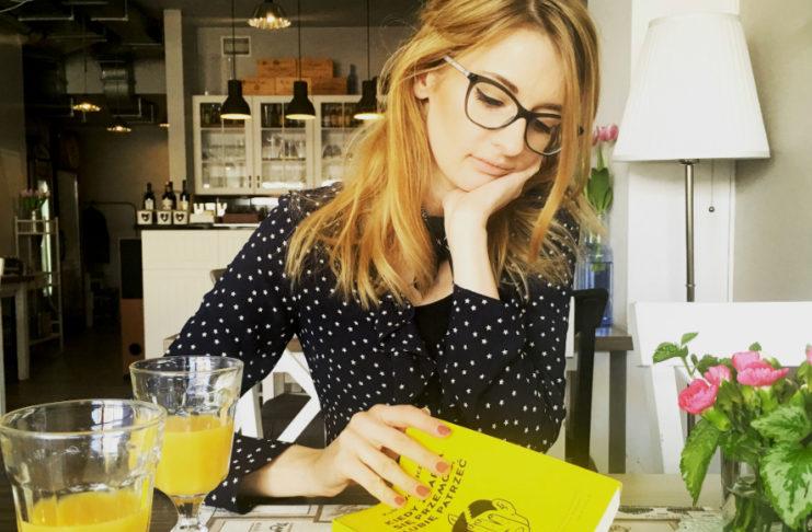Kobieta siedząca przy stole w ciemnej bluzce, trzymająca w ręku książkę