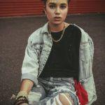 Dziewczyna w koczkach na głowie,, czarnej bluzce, jeansowej kurtce i jeansowych poszarpanych spodniach