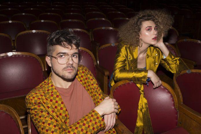 Para ubrana w stylu retro, siedzaca w sali kinowej