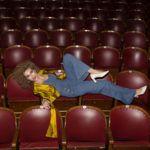 Kobieta leżąca na fotelach w sali kinowej