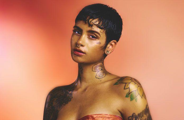 Kobieta z krótki włosami i widocznymi na ramionach tatuażami, na różowo pomarańczowym tle