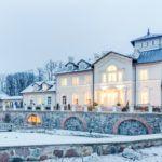 Zabytkowy pałac w trakcie zimy, opruszony śniegiem