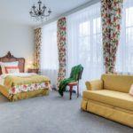 Pokój z dużym podwójnym łóżkiem, żółto-pomarańczową kanapą i zabytkową komodą
