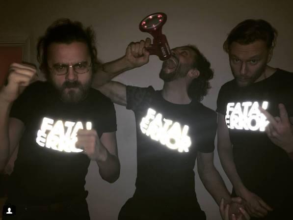 Trzech mężczyzn ubranych w czarne koszulki z błyszczącym napisem Fatal Error