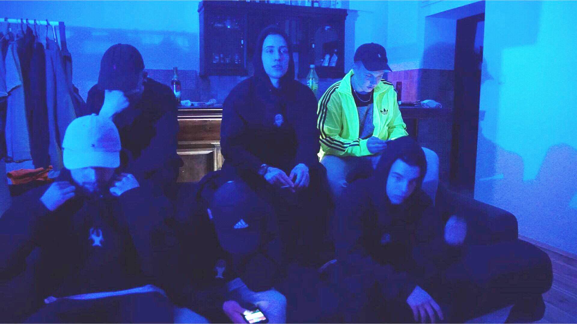 Pięciu chłopaków ubranych w dresy w ciemnym pokoju