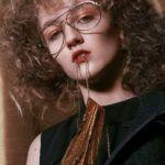 Dziewczyna z kręconymi włosami, w okularach, trzymająca łańcuszek w ustach