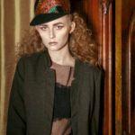 Blondwłosa dziewczyna w czapce stojąca przy szafie