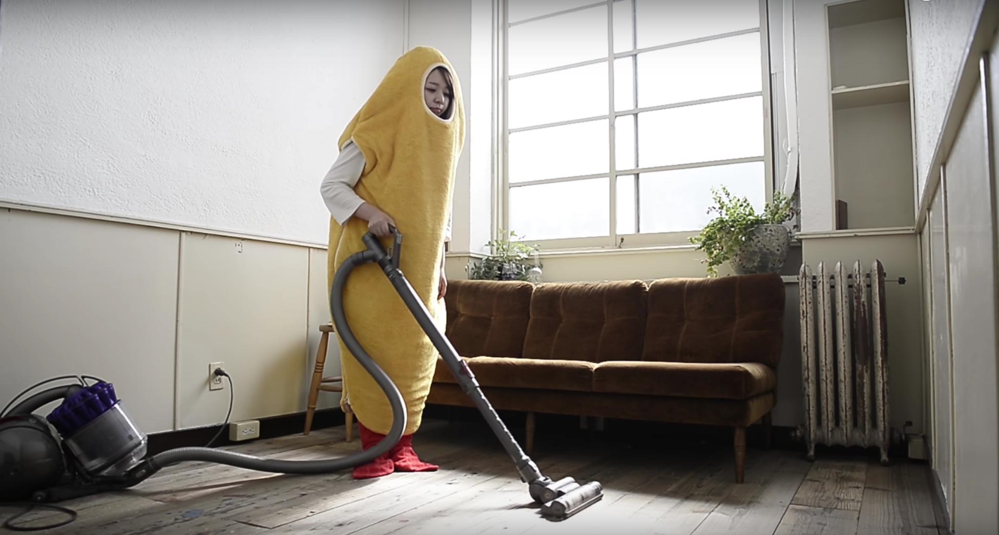Kobieta w przebraniu krewetki odkurząjąca mieszkanie