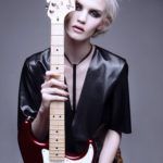 Dziewczyna ubrana na czarno trzyma czerwono-białą gitarę elektryczną