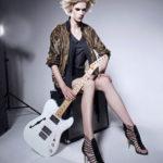 Dziewczyna ubrana w buty na obcasie, czarny strój i brązowo-złoty sweter, trzyma w ręku miętową gitarę elektyczną