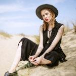 Blondynka w czarnym kapeluszu i sukience siedząca na wydmie