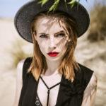 Blondynka w czarnym kapeluszu i czarnej sukience