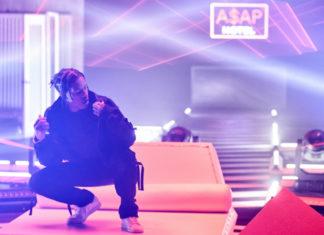 Czarnoskóry mężczyzna kucający na scenie, w tle neonowe światła