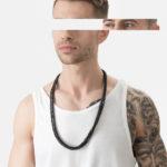 Mężczyzna w białej koszulce i czarnym naszyjniku