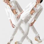 Dwie kobiety ubrane w białę spodnie, białą marynarkę i biały biustonosz