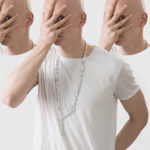 Mężczyzna ubrany w biały tshirt zakrywający twarz dłonią