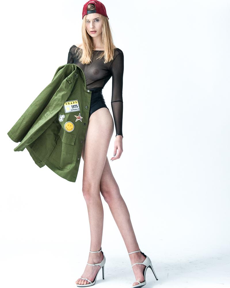 Kobieta w siateczkowym body z długim rękawem, w szpilkach, z zieloną kurtką w ręku