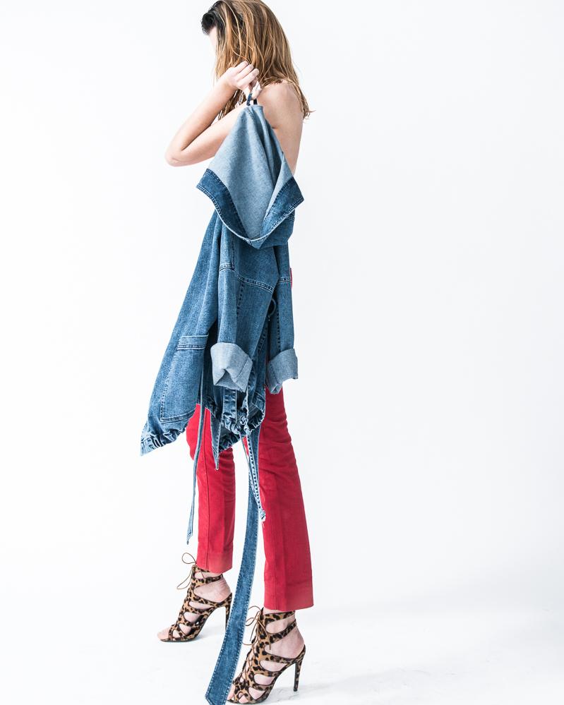 Kobieta stojąca tyłem, w szpilkach, czerwonych spodniach z jeansową kurtką z kapturem w ręku