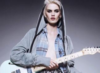 Dziewczyna ubrana w szarą bluzę i koszulę w kratę trzymająca gitarę elektryczną