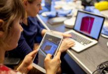 Dwie kobiety, jedna siedzi przy laptopie, druga trzyma w dłoniach tablet
