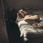 Dziewczyna z bieliźnie leżaca na łóżku, lewa ręka częściowo zakrywa twarz