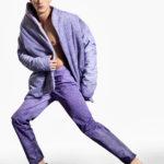 Mężczyzna w czarnych pantoflach, fioletowych spodniach i fioletowej kurtce bez koszulki pod spodem