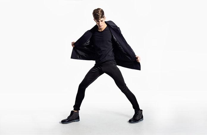 Mężczyzna ubrany na czarno trzymający rogi kurtki
