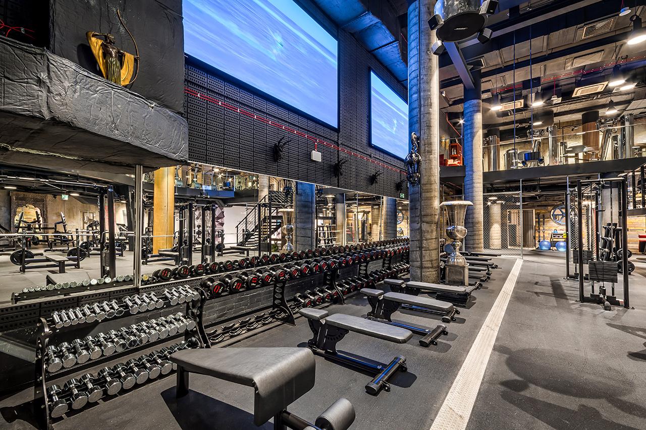 Wnętrze siłowni, dwa duże ekrany oraz przyrządy i urządzenia do ćwiczeń