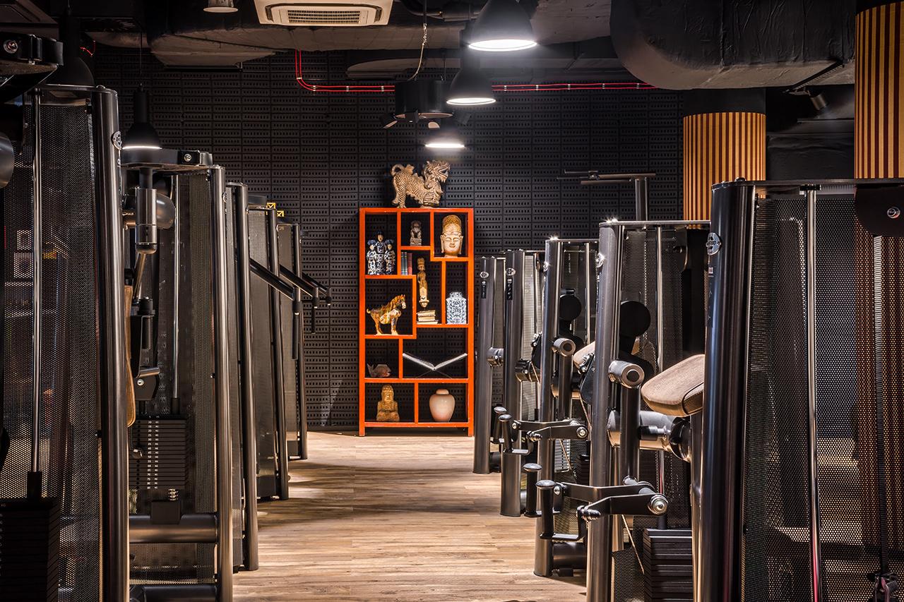 Wnętrze siłowni z widoczną pomarańczową szafką przy ścianie