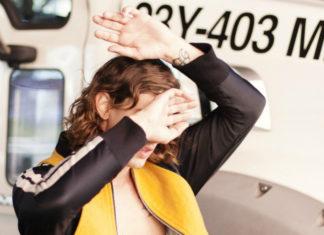 Mężczyzna z włosami do ramion ubrany w żółtą kurtkę zasłania twarz rękoma, w tle widać fragment ciężarówki