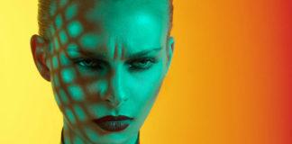 Kobieta z zielonym światłem na twarzy stojąca na żółtym tle