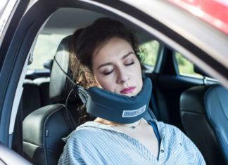 Kobieta siedząca na siedzeniu pasażera ucinająca sobie drzemkę z włożoną pod brodę poduszką zahaczoną o zagłówek