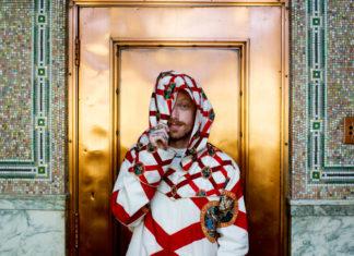 Mężczyzna w chustce na głowie stojący na tle złotych drzwi