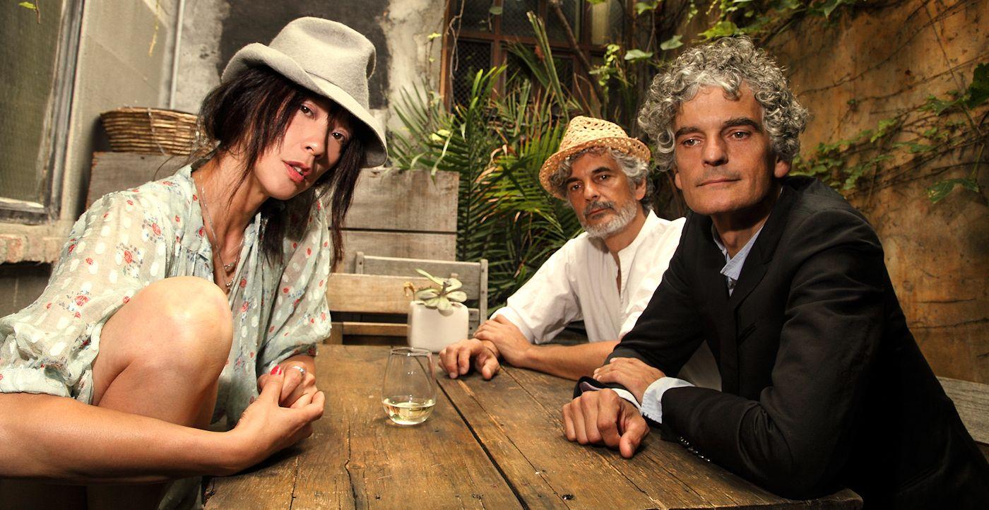 Dwóch mężczyzn i kobieta w kapeluszu siedzący przy drewnianym stole