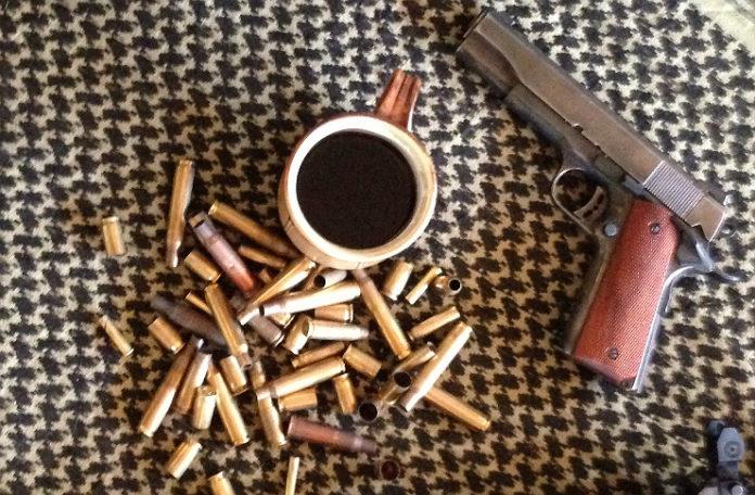 Kubek kawy, obok naboje i pistolet