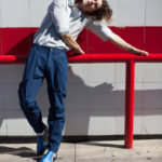 Mężczyzna w ciemno niebieskich spodniach i jano niebieskiej koszuli opiera się o czerwoną barierkę