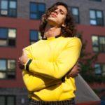 Mężczyzna z włosami do ramion ubrany w żółtą bluzę z rękami złożonymi na piersi