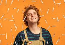 Mężczyzna w bluzce w paski i ogrodniczkach na pomaranczowym tle z papierosami
