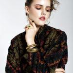 Kobieta ubrana w ciemne futro, jedną ręką trzymają się za twarz