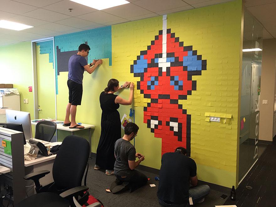 Pracownicy biura przyklejący do ścian samoprzylepne karteczki, które tworzą obrazek Spidermana