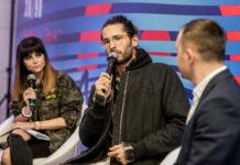 Kobieta ubrana w kurtkę moro, mężczyzna trzymający mikrofon i mężczyzna siedzacy tyłem do obiektywu aparatu