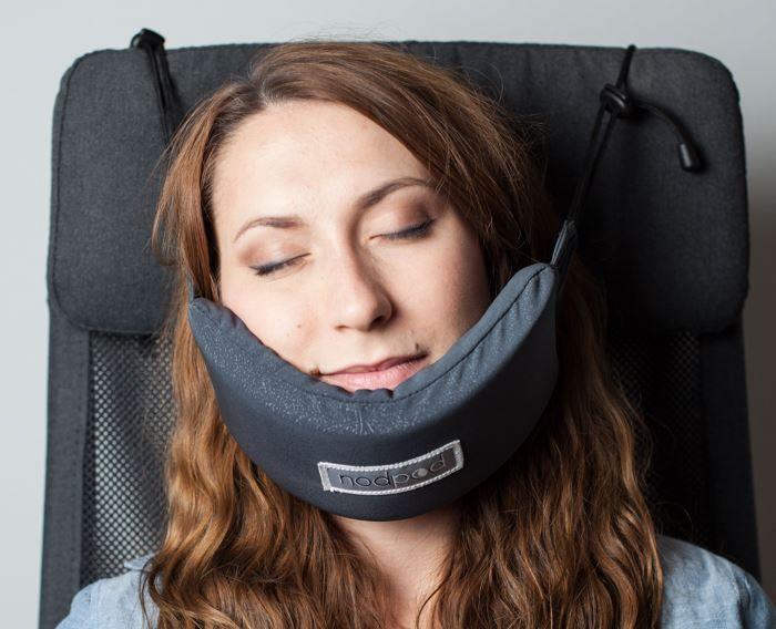 Kobieta siedząca na fotelu, ucinająca sobie drzemkę z poduszką pod brodą, która jest zaczepiona o zagłówek