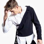 Mężczyzna poprawiający jedną ręką włosy, ubrany w czarne spodnie, białą koszulę i bluzę założoną na jedno ramie