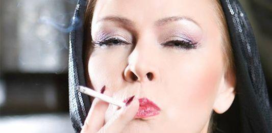 Kobieta z przymrużonymi oczami zaciągająca się papierosem